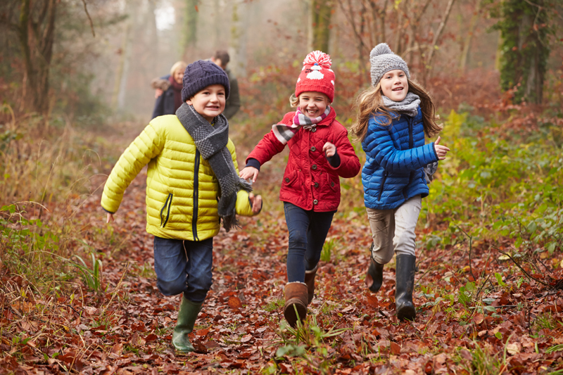 three children running in the woods